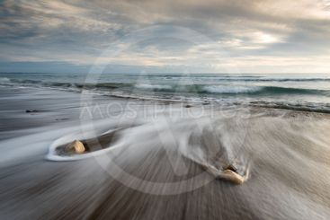 Pebbles in the beach and flowing sea water