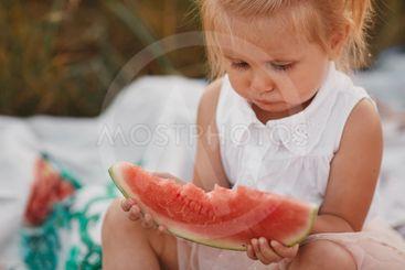 Child eating watermelon in the garden. Kids eat fruit...