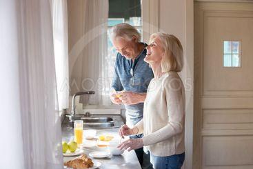 Happy senior couple having fun preparing breakfast in the...