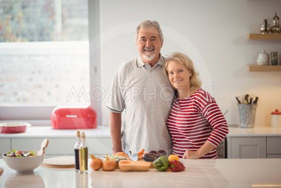 Smiling senior couple standing together in kitchen