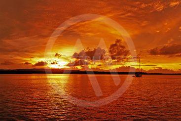 Golden and orange colored coastal cloudy sunrise seascape.