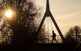 silhouette of man walking in bridge under the river by...