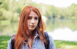 authentic young woman wearing denim jacket and backpack...