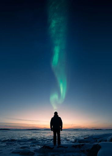 A man standing on ice an looking at sunset with Aurora...