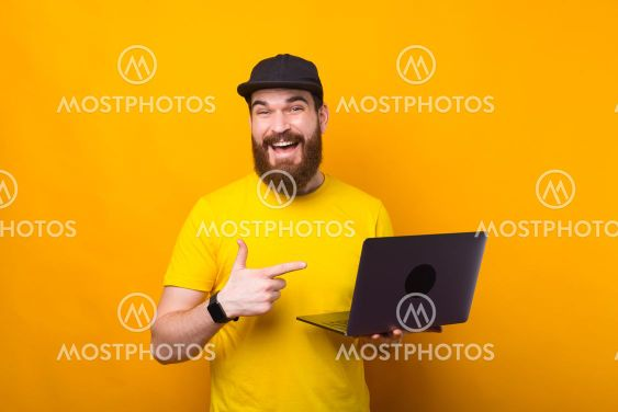 Charming bearded hipster man pointing at his new laptop...