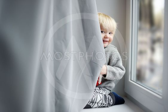 Toddler boy on the window sill