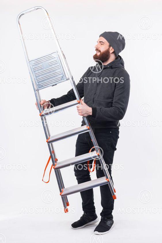 Full length photo of bearded man holding portable metal...