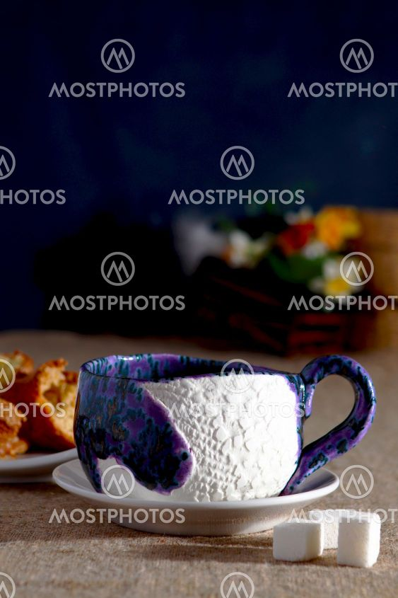 Ceramic cup with sugar cake on the plate on black...
