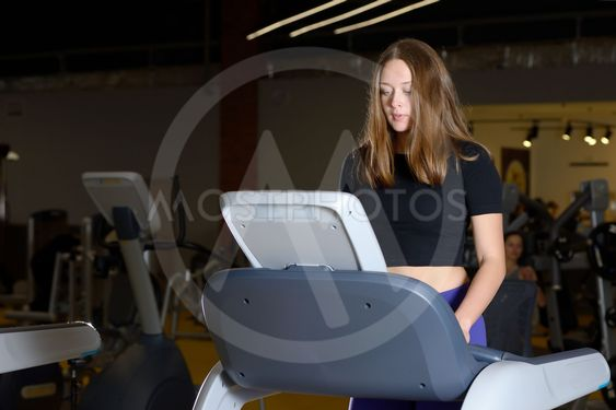 Attractive young woman doing cardio exercise on treadmill...