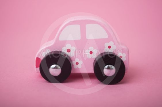 pink miniature wooden car on pink background