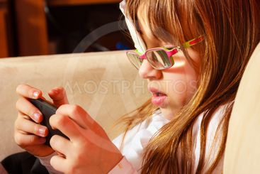 girl child in glasses playing games on smartphone at home