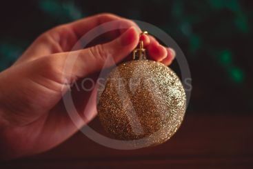 Hand keeps a golden Christmas ball on green and brown...
