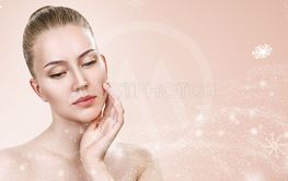 Young woman over beige background with snowflakes.