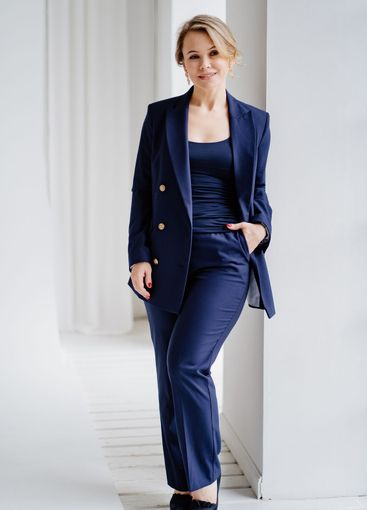 blonde woman in a blue suit poses standing in a photo...