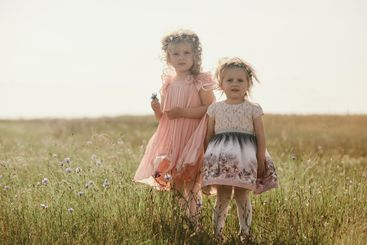 Portrait of two sisters with bouquets of wildflowers. On...