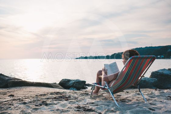 Young woman reading a book on the beach
