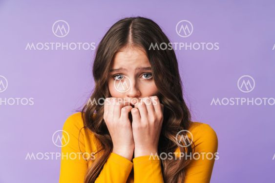 Image of young caucasian woman being scared and biting...
