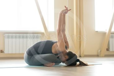 Young woman doing Padmasana pose with forward bend,...