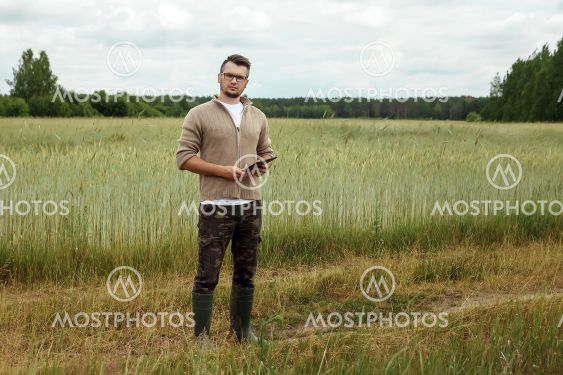 The man is a farmer, standing in his field. Farmland,...