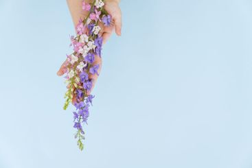 blue, pink and white flowers in hands, blue...