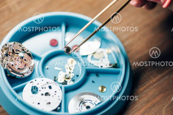 Cropped view of watchmaker holding watchpart in tweezers...