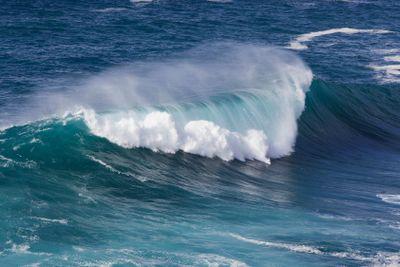 En våg bryts vid stranden