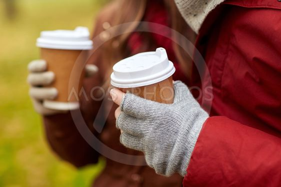 close up of couple hands with coffee in autumn