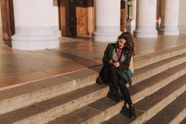 Young pretty lady resting on stairs outdoors