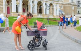 Stylish mother attending to her infant in a pram