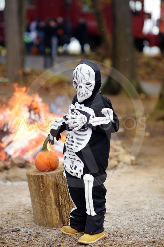 Little boy in scary skeleton costume on background of...