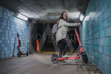 Woman standing on an electric scooter