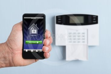 Person Holding Remote Control Of Security System