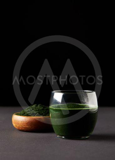 fresh spirulina drink in glass and spirulina powder in...