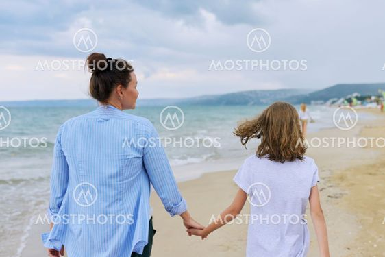 Happy mom and daughter walking on the sea beach holding...