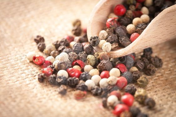 Red, white and black pepper in a spoon