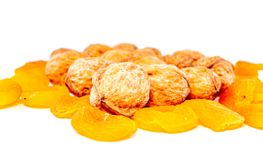 Walnuts and dried apricots on a white background with...