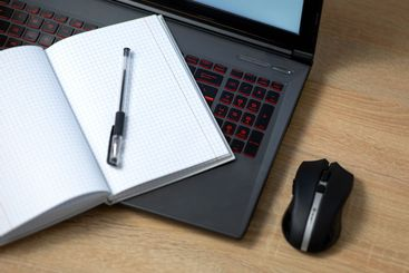 Laptop with wireless mouse, notebook and pen