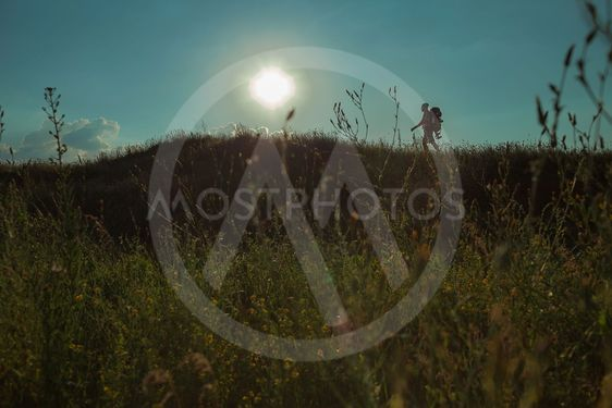 Young caucasian man with backpack walking on a green meadow