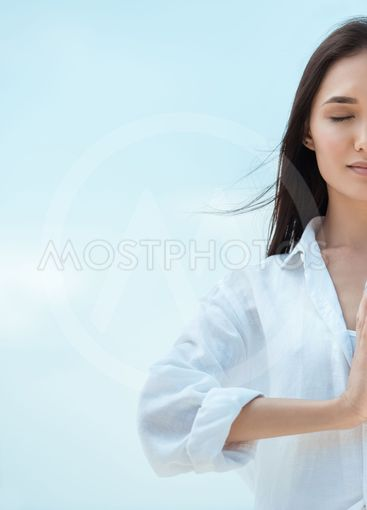 partial view of asian woman with closed eyes doing...
