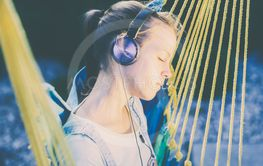 young girl listening to music with headphones lying in a...