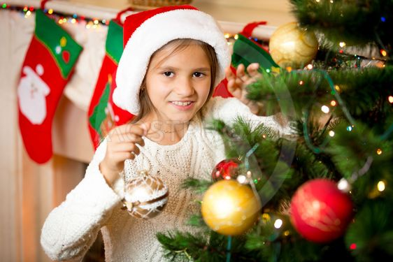 cute smiling girl decorating Christmas tree with golden...