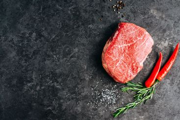 Raw beef steak on black background with rosemary, chili...