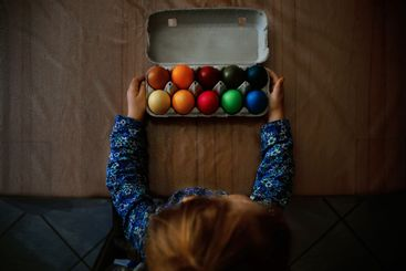 Close-up of little toddler girl with colored eggs for...