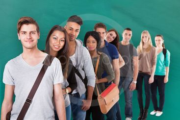 Student Standing In Row Against Green Background
