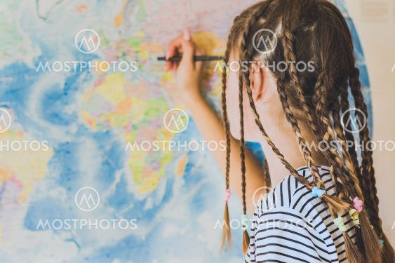 Teenage girl with pigtails makes pencil marks on the...