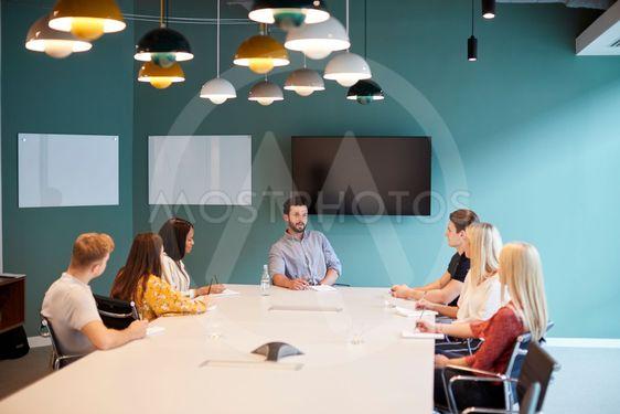 Businessman Addressing Group Of Candidates Meeting Around...