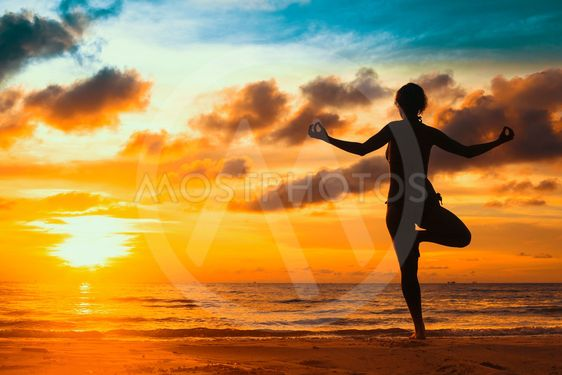 Silhouette young woman practicing yoga on the beach at...