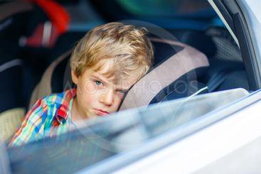 Sad tired kid boy sitting in car  during traffic jam
