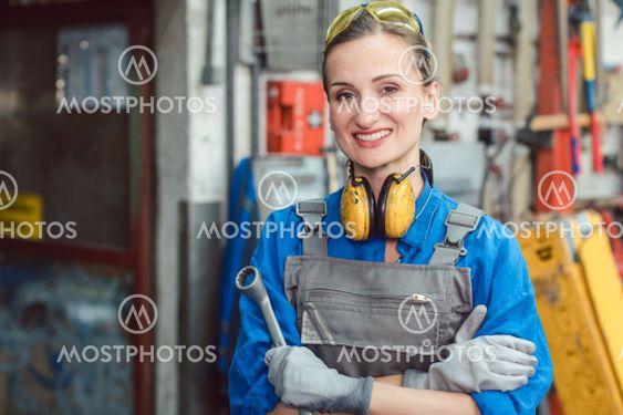 Woman worker in her metal workshop posing with tools