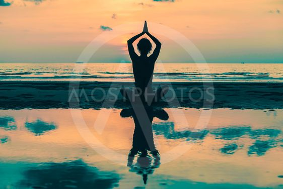 Yoga Silhouette. Woman on the beach with reflection in...